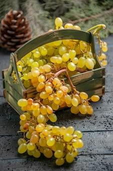 Vista lateral de close-up uvas brancas uvas brancas apetitosas em caixa de madeira na mesa cinza ao lado de ramos de abeto e cones