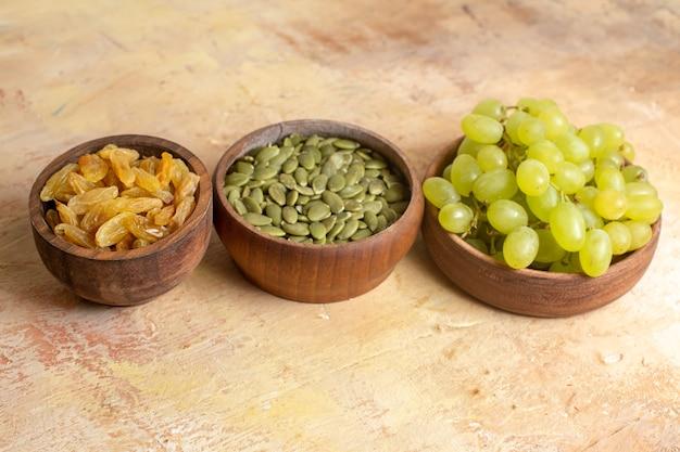 Vista lateral de close-up uvas passas apetitosas uvas verdes sementes de abóbora em tigelas marrons
