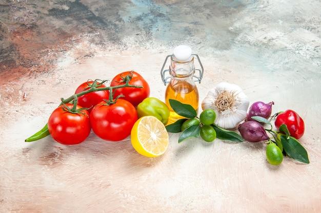 Vista lateral de close-up vegetais tomates óleo pimentão cebola alho pimenta pimenta limão