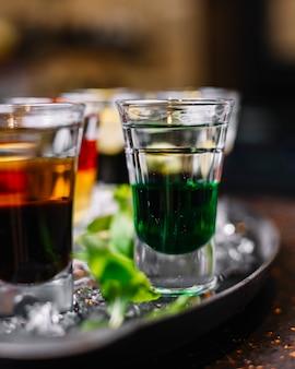 Vista lateral de cocktails coloridos em copos de shot