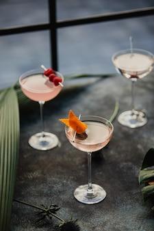 Vista lateral de cocktails rosa decorados com frutas em um copo em cima da mesa