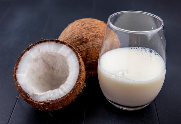 Vista lateral de coco fresco e marrom com um copo de leite na superfície preta