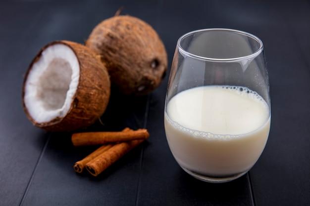 Vista lateral de cocos com um copo de leite e paus de canela na superfície preta