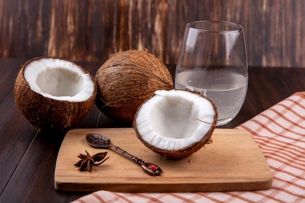 Vista lateral de cocos frescos em uma placa de cozinha de madeira com colher e um copo de água na toalha xadrez e superfície de madeira