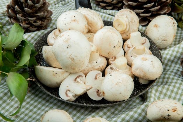 Vista lateral de cogumelos brancos frescos em uma frigideira e cones com folhas verdes em tecido xadrez