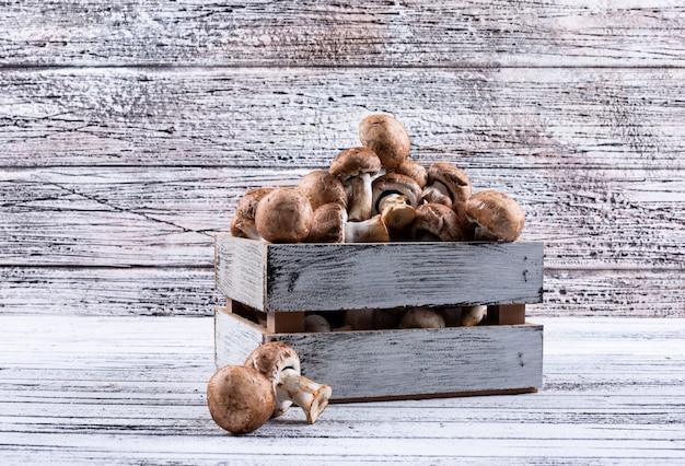 Vista lateral de cogumelos em caixa de madeira na mesa de madeira clara