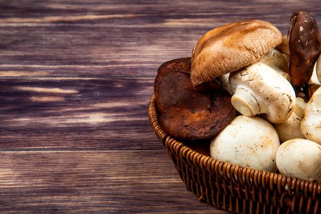 Vista lateral de cogumelos frescos em uma cesta de vime em madeira rústica, com espaço de cópia