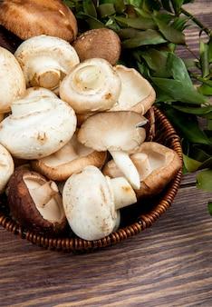 Vista lateral de cogumelos frescos em uma cesta de vime em madeira rústica