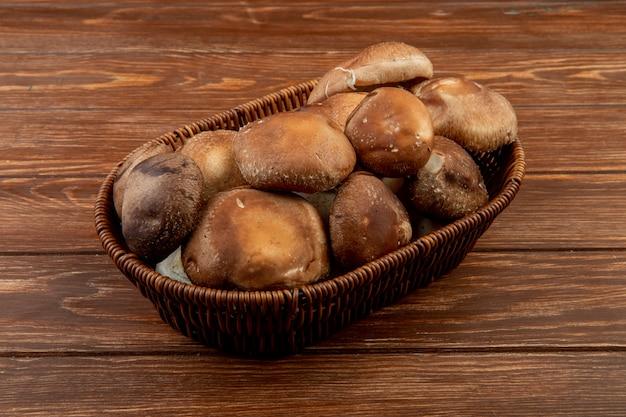 Vista lateral de cogumelos frescos em uma cesta de vime na madeira rústica