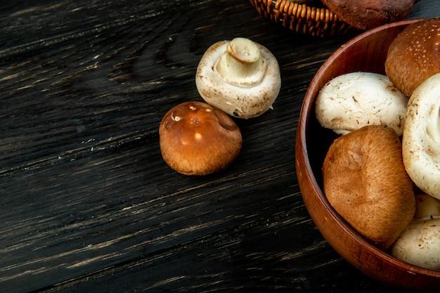 Vista lateral de cogumelos frescos em uma tigela em madeira escura, com espaço de cópia