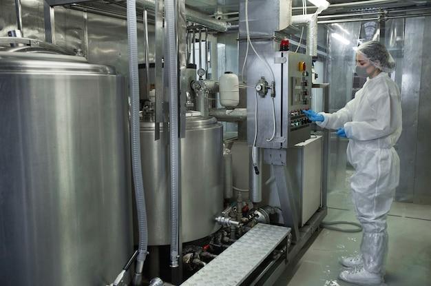Vista lateral de comprimento total em unidades de máquina operando jovem trabalhadora enquanto trabalhava em uma fábrica de alimentos limpos, copie o espaço
