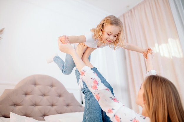Vista lateral de comprimento total mãe jovem feliz, deitado na cama, levantando a filha criança pré-escolar. garota garoto pequeno fazendo avião, se divertindo com mamãe forte juntos no quarto
