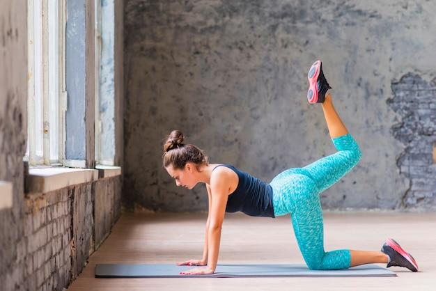 Vista lateral, de, condicão física, mulher jovem, esticar, dela, pernas, em, sótão