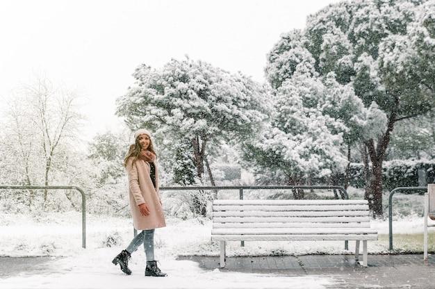 Vista lateral de conteúdo mulher em agasalhos caminhando em um parque nevado enquanto aproveita o inverno