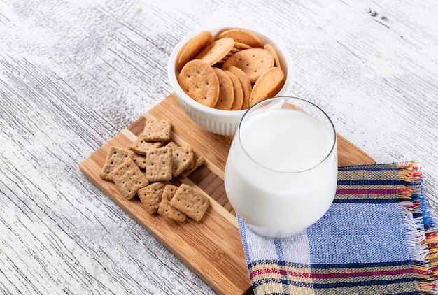 Vista lateral de cookies com leite na mesa de madeira horizontal