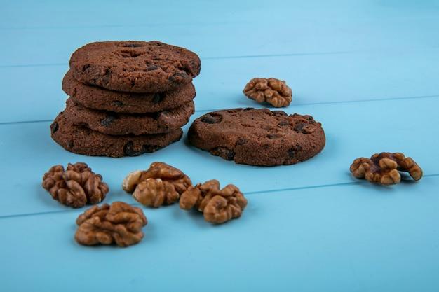 Vista lateral de cookies de brownie de manteiga de amendoim sem farinha e nozes sobre fundo azul
