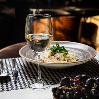 Vista lateral de copo de vinho com macarrão e uva em prato redondo