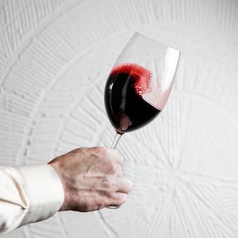Vista lateral de copo de vinho tinto com mão humana