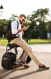 Vista lateral de corpo inteiro de homem barbudo em óculos de sol, sentado na moto moderna ao ar livre e usando o smartphone
