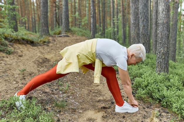 Vista lateral de corpo inteiro de mulher de meia-idade em forma desportiva, alongando a perna antes de correr, com os pés afastados e tocando os dedos dos pés com as mãos.