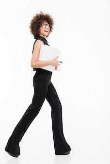 Vista lateral de corpo inteiro de uma jovem empresária bem-sucedida