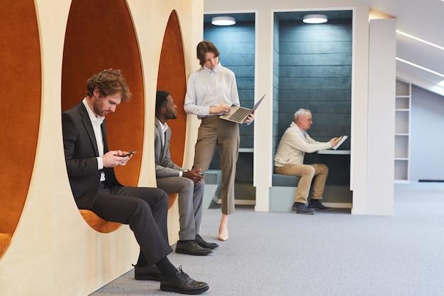 Vista lateral de corpo inteiro em um grupo multiétnico de empresários trabalhando no interior contemporâneo de um escritório ou centro de coworking, copie o espaço