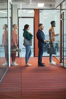 Vista lateral de corpo inteiro em um grupo multiétnico de executivos em pé na fila no interior de um escritório moderno, copie o espaço