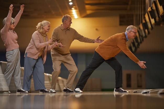 Vista lateral de corpo inteiro para um grupo de idosos empolgados jogando boliche enquanto desfruta de entretenimento ativo na pista de boliche, copie o espaço