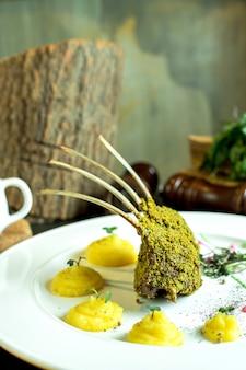 Vista lateral de costelas de cordeiro assado com purê de batatas no prato