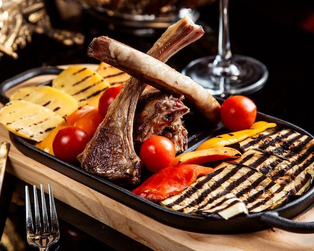 Vista lateral de costelas de cordeiro fritas, guarnecidas com legumes grelhados e tomates frescos em cima da mesa