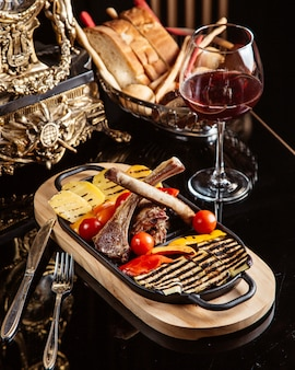Vista lateral de costelas de cordeiro frito com batatas grelhadas tomates frescos e copo de vinho tinto em cima da mesa