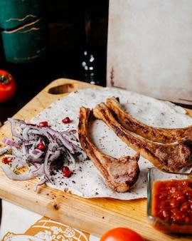 Vista lateral de costelas de cordeiro kebab com cebola roxa e romã em uma placa de madeira