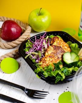 Vista lateral de costeleta de brócolis e batata, servido com salada de repolho em uma caixa de entrega na mesa de madeira