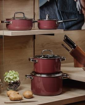 Vista lateral de cozinhar conjunto de tachos e panelas nas prateleiras de madeira jpg