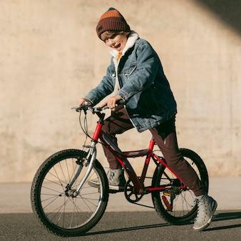 Vista lateral de criança de bicicleta ao ar livre se divertindo