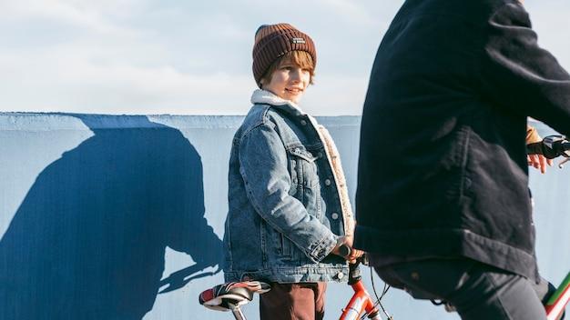 Vista lateral de crianças andando de bicicleta ao ar livre