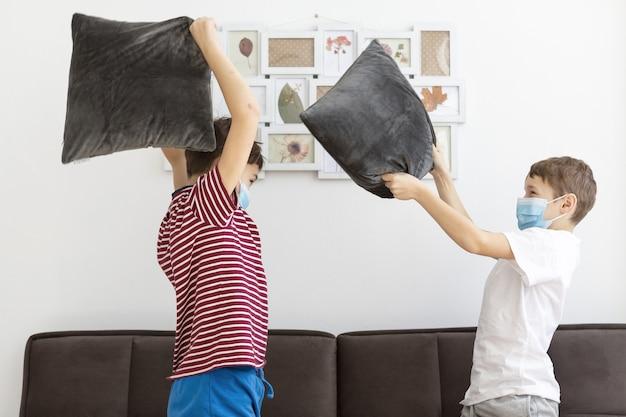 Vista lateral de crianças com máscaras médicas brincando com almofadas