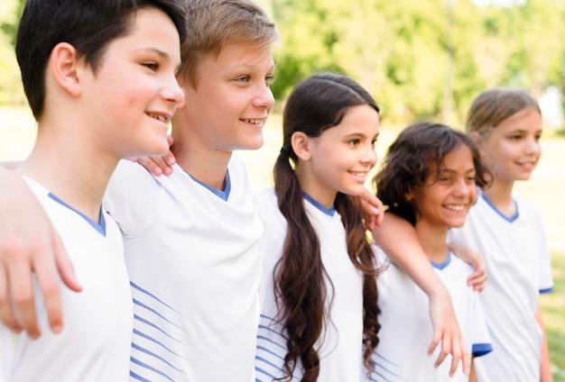 Vista lateral de crianças em roupas esportivas abraçadas