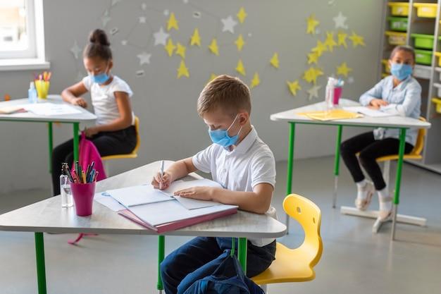Vista lateral de crianças fazendo anotações na aula enquanto usam máscaras médicas