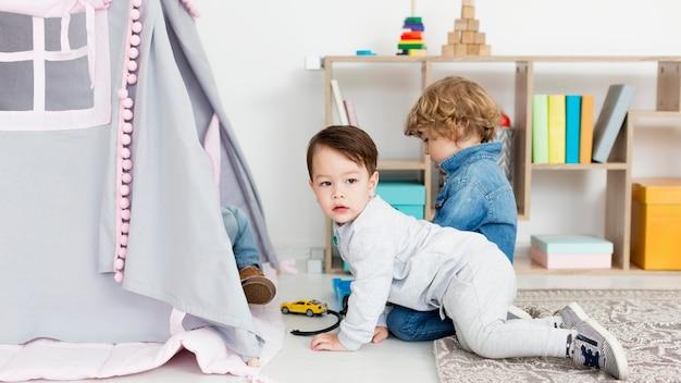 Vista lateral de crianças fora da barraca com brinquedos