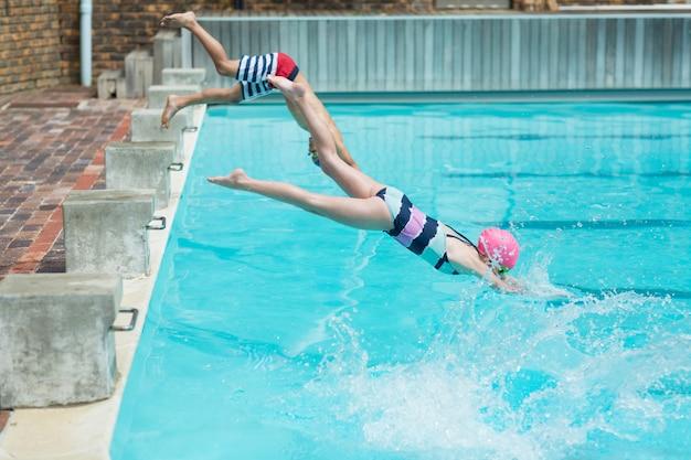 Vista lateral de crianças mergulhando na água à beira da piscina