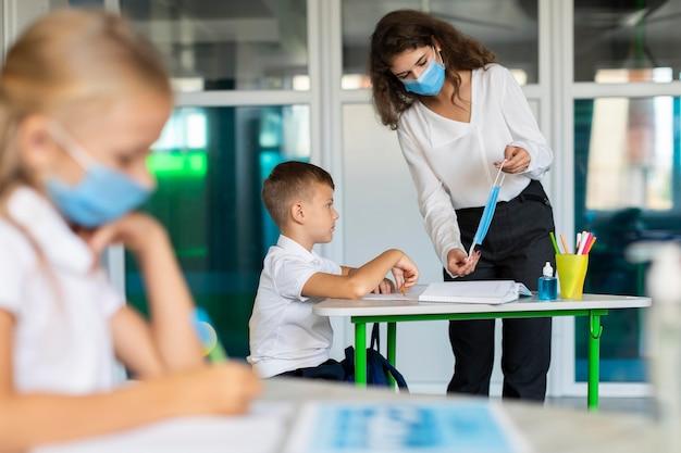 Vista lateral de crianças sentadas em suas mesas enquanto se distanciam socialmente