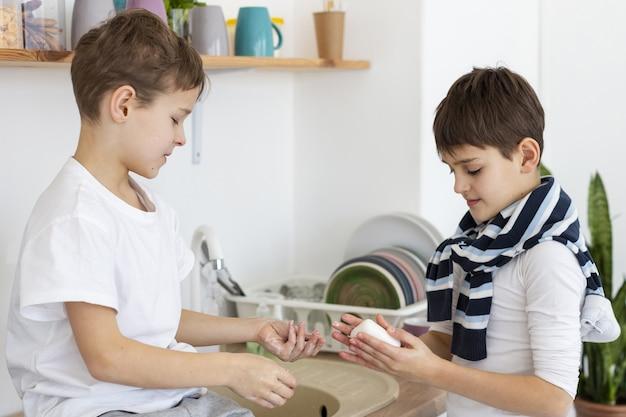 Vista lateral de crianças usando sabão para lavar as mãos