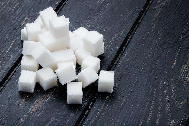 Vista lateral de cubos de açúcar, dispostos em fundo preto de madeira, com espaço de cópia
