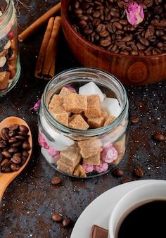 Vista lateral de cubos de açúcar mascavo em uma jarra de vidro e grãos de café em uma tigela sobre fundo preto