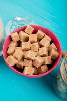 Vista lateral de cubos de açúcar mascavo em uma tigela rosa sobre fundo azul de madeira
