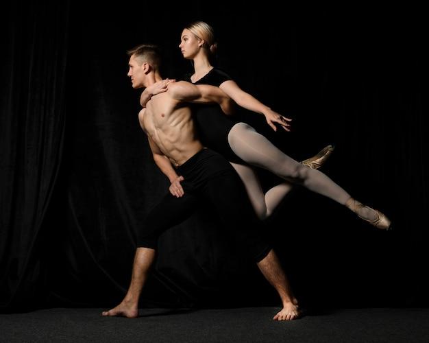 Vista lateral de dançarinos de balé posando