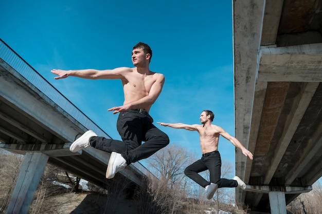 Vista lateral de dançarinos de hip hop posando no ar