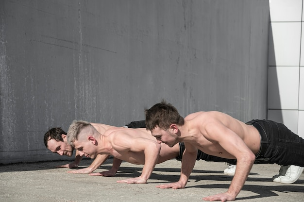 Vista lateral de dançarinos de hip hop sem camisa ensaiando lá fora