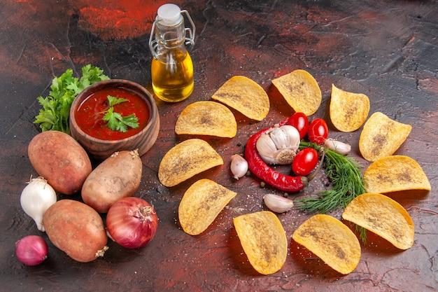 Vista lateral de deliciosas batatas fritas caseiras crocantes pimenta vermelha alho tomate verde ketchup batatas cebola garrafa de óleo na mesa escura